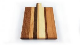 Chopping and serving board constructed from various widths of different hardwood timbers to create an attractive stripped pattern cutting surface. With rounded over edges for easy lifting.